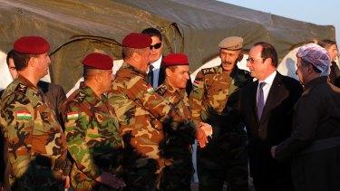 President of the Iraqi self-ruled Kurdish region, Massoud Barzani, right, introduces French President Francois Hollande to Kurdish Peshmerga soldiers.