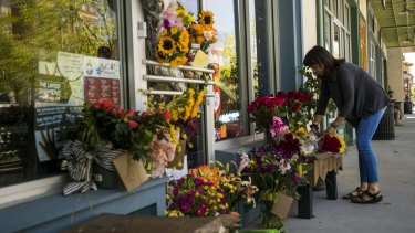 A woman leaves a bouquet of flowers at a makeshift memorial for store co-owner Jillian Johnson at Red Arrow Workshop in River Ranch in Lafayette on Friday.