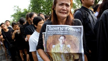 A Thai woman weeps as she holds on to a portrait of King Bhumibol Adulyadej.