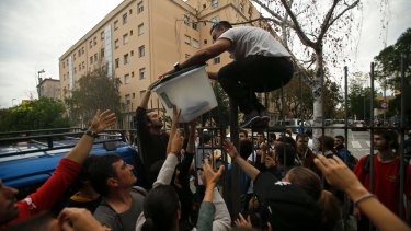 A ballot box is taken from a school in Girona assigned to be a polling station by the Catalan government.