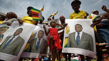 A young girl marches in position as she mimics the military parade, accompanied by supporters holding posters of President Emmerson Mnangagwa, at his inauguration.