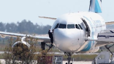 A man leaves the hijacked aircraft of Egyptair from a pilot window.