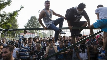 Refugees climb a border fence that separates Serbia from Hungary before violence broke out on Wednesday.