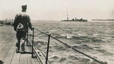 An unidentified seaman on the quarter deck of HMAS Sydney looks at the wrecked German cruiser Emden