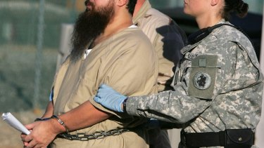 A shackled detainee is transported by a female guard at Guantanamo Bay in 2006.