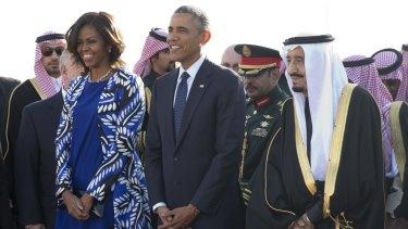 President Barack Obama and first lady Michelle Obama stand with new Saudi King Salman bin Abdul Aziz at Riyadh airport.