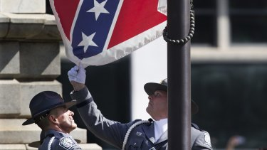 An honour guard from the South Carolina Highway patrol lowers the Confederate battle flag as it is removed from the Capitol grounds  in Columbia, South Carolina.