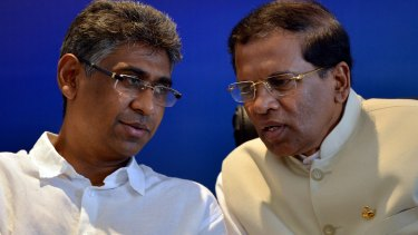 Sri Lanka's main opposition presidential candidate Maithripala Sirisena, right, listens to Investment Promotion Deputy Minister Faizer Mustapha at a press conference in Colombo on Wednesday.