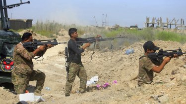 Iraqi security forces fire at Islamic State militants in Fallujah.