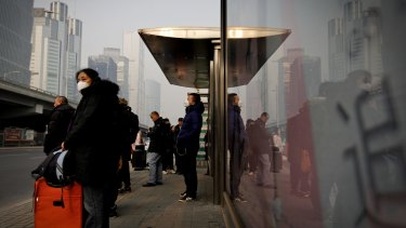 Commuters wearing protection masks wait for buses at a bus stand on a polluted day in Beijing last year.