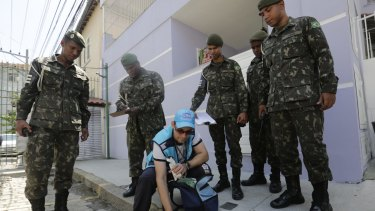 Surrounded by soldiers, a government health agent uses larvicide to kill mosquitos that spread the Zika virus, in the Tijuca neighbourhood of Rio de Janeiro, Brazil, on Monday.