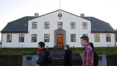 People walk past the Icelandic Prime Minister's office in Reykjavik.