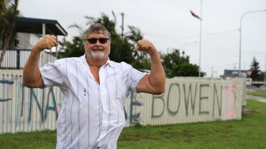 Graham Wilson paints a fresh message on his fence in the wake of Cyclone Debbie.