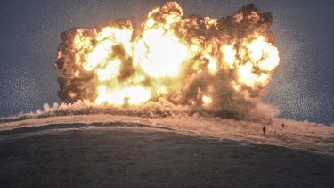 This October 23 photo shows militants of Islamic State as they stand next to the explosion of an air strike on Tilsehir Hill near the Turkish border, at Yumurtalik village.