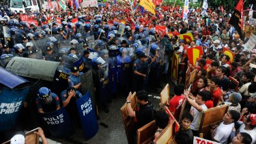 Thousands of anti-government protesters clash with riot police during their march towards the House of Representative to coincide with Benigno Aquino III's address.