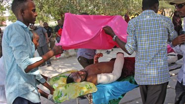Somalis help a civilian wounded in Saturday's blast.