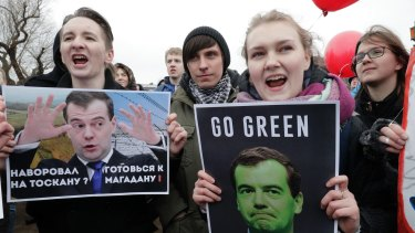 Protesters hold posters depicting Russian Prime Minister Dmitry Medvedev who is accused of corruption.