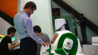 A visitor with a robot at a convention in St Petersburg last week.