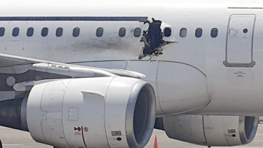 The plane operated by Daallo Airlines sits on the runway in Mogadishu. A gaping hole in the commercial airliner forced it to make an emergency landing in Somalia's capital.