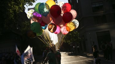 A balloon seller walks past people on the way to the closing rally of presidential candidate Alejandro Guillier in Santiago.