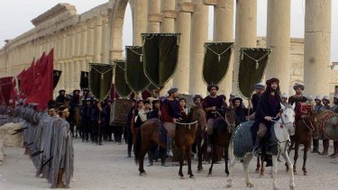 In this 2002 file photo, a symbolic trade caravan representing the prosperous trade during the era of Queen Zenobia AD260-AD273 attend a show in the ancient city of Palmyra.