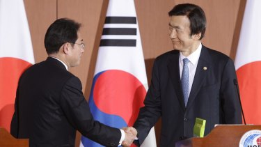 South Korean Foreign Minister Yun Byung-Se (right) shakes hands with Japanese Foreign Minister Fumio Kishida after their joint news conference.