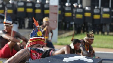 Indigenous protesters from various ethnic groups take cover during clashes with riot police in Brasilia.