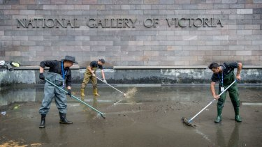 Cleaners work on the moat at the NGV. The collected coins are recorded as NGV donations and will go towards the acquisition of art.