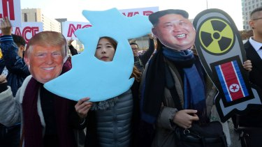 Anti-war protesters wearing cutouts of US President Donald Trump and North Korean leader Kim Jong-un, march demanding peace on the Korean peninsula near the American Embassy in Seoul on Sunday.