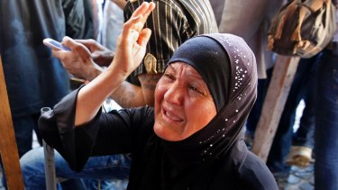 The mother of Mustafa Ali Wehbe, who was kidnapped by IS, weeps. Bodies believed to be of kidnapped soldiers have been found buried near the Lebanese border with Syria.
