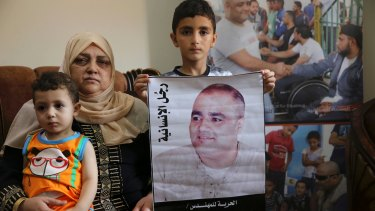 Amal al-Halabi, 57, holds her grandson Fares while her grandson Amro, 7, holds a poster demanding freedom for his father Mohammed al-Halabi, Gaza director of  World Vision.