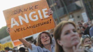 """A supporter of the German Christian Democrats holds up a sign that reads: """"Thanks Angie, keep going!"""" in reference to German Chancellor Angela Merkel."""