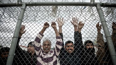 Immigrants stand behind a fence at the Amygdaleza detention centre in western Athens on February 14.