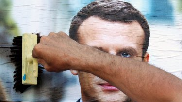 A supporter of French centrist presidential candidate Emmanuel Macron glues a campaign poster in Bayonne, south-western France.