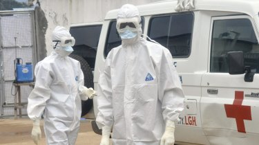 Health workers in Liberia prepare to remove the body of an Ebola victim.