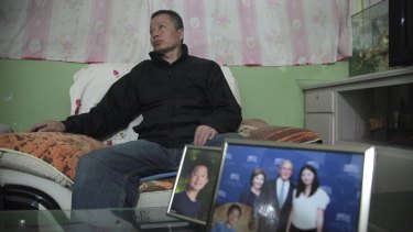 Gao Zhisheng listens to journalists in a cave home while sitting near photos of his son and and daughter in this photo taken earlier this year.