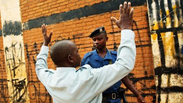 Police search a Burundi citizen as he tries to walk into a polling station during parliamentary and local elections late last month.