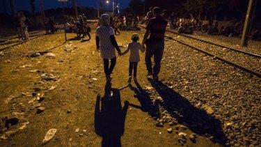 A family walks along the train tracks at dusk at the Greek Macedonian border  in Idomeni, Greece.