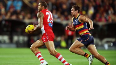 Lance Franklin of the Swans is pursued by Kyle Hartigan of the Crows as he moves upfield.