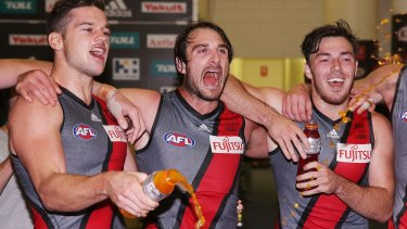 Bombers Patrick Ambrose, Jobe Watson and Michael Hibberd  celebrate the win over St Kilda this year wearing the grey jumper.