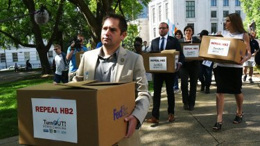 The executive director of Equality North Carolina, Chris Sgro, leads a group carrying petitions calling for the repeal of House Bill 2 to governor Pat McCrory's office.