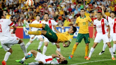 Up in the air: Tim Cahill opens the scoring against China in some style.