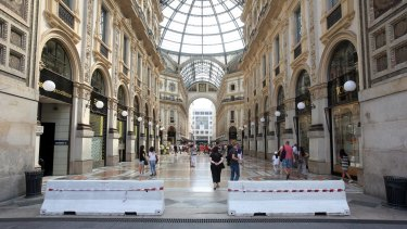 Hastily placed barriers to prevent vehicles from entering greet tourists at the Vittorio Emanuele gallery in Milan.