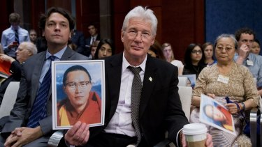 American actor and activist Richard Gere holds a photo of Tulku Tenzin Delek Rinpoche, one of the most respected and revered Tibetan lamas, who died in custody in a Chinese prison on July 12.