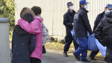 Police officers carry a dead body past the relatives after the body was found at a site collapsed by an earthquake in Mashiki, Kumamoto prefecture, on Saturday.