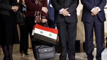 A member of the Syrian government holds a bag with the colours of the Syrian flag at a press conference in Geneva on Monday.