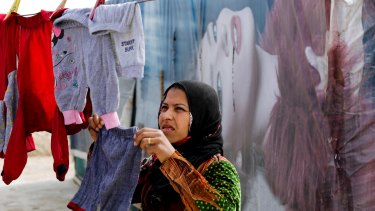 A Syrian hangs her laundry at an informal refugee camp in the Bekaa Valley town of al-Marj.