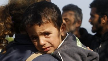 A boy on his mother's shoulder as they enter into Macedonia from Greece on the border  between the two countries on Tuesday.