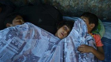 Children sleep on the floor outside the station.