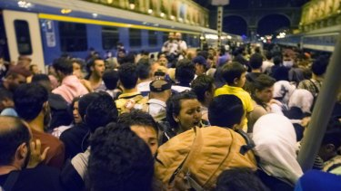Migrants wait to board a train to Germany.